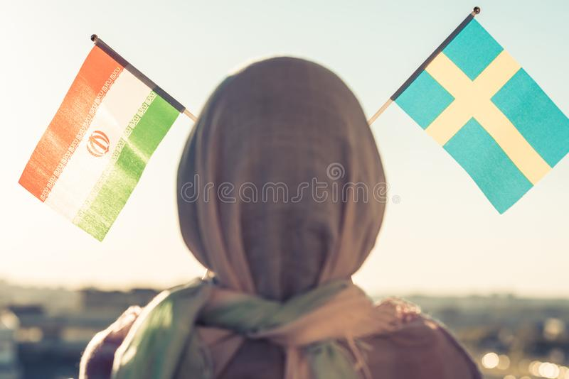 Muslim woman in scarf with Swedish and Iranian flags of at sunset.Concept. Muslim woman in scarf with Swedish and Iranian flags of at sunset.Concept royalty free stock image