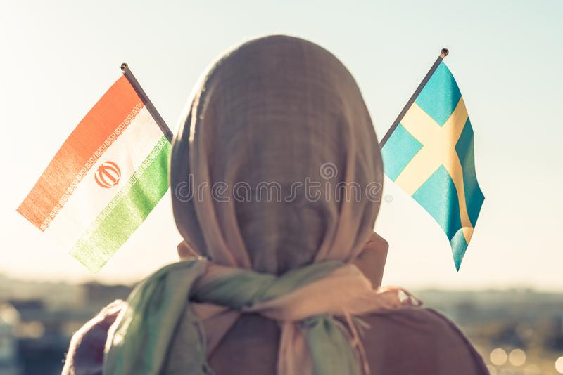 Muslim woman in scarf with Swedish and Iranian flags of at sunset.Concept. Muslim woman in scarf with Swedish and Iranian flags of at sunset.Concept stock images