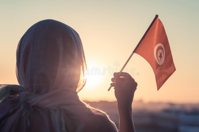 Muslim woman in scarf with Tunisia flag of at sunset.Concept. stock photo