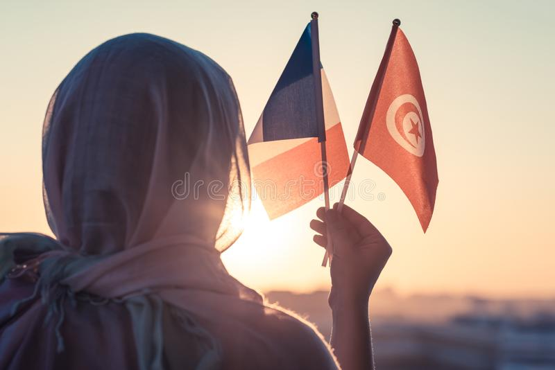 Muslim woman in scarf with Tunisia and French flags of at sunset.Concept. Muslim woman in scarf with Tunisia and French flags of at sunset.Concept stock images