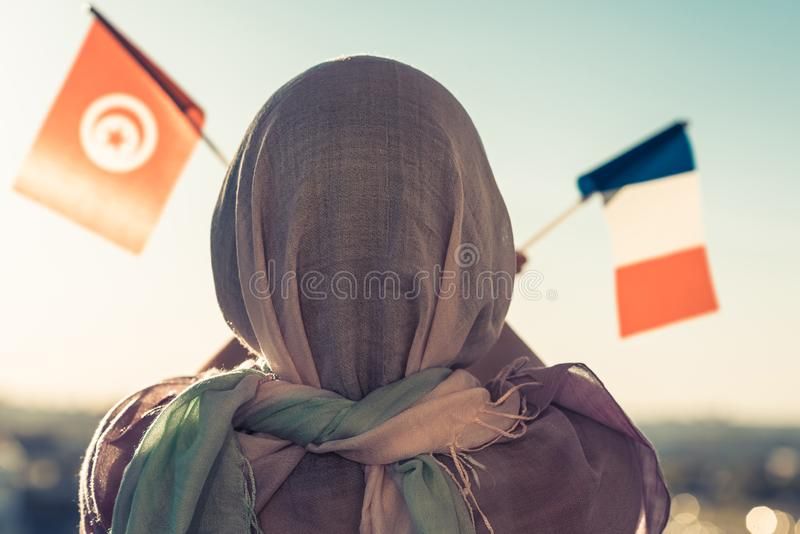 Muslim woman in scarf with Tunisia and French flags of at sunset.Concept. Muslim woman in scarf with Tunisia and French flags of at sunset.Concept stock photo