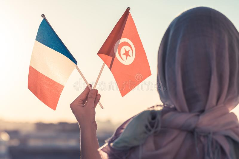 Muslim woman in scarf with Tunisia and French flags of at sunset.Concept. Muslim woman in scarf with Tunisia and French flags of at sunset.Concept stock image