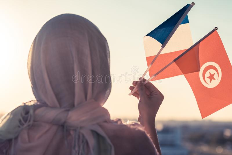 Muslim woman in scarf with Tunisia and French flags of at sunset.Concept. Muslim woman in scarf with Tunisia and French flags of at sunset.Concept stock photography