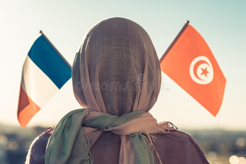 Muslim woman in scarf with Tunisia and French flags of at sunset.Concept. Muslim woman in scarf with Tunisia and French flags of at sunset.Concept royalty free stock images