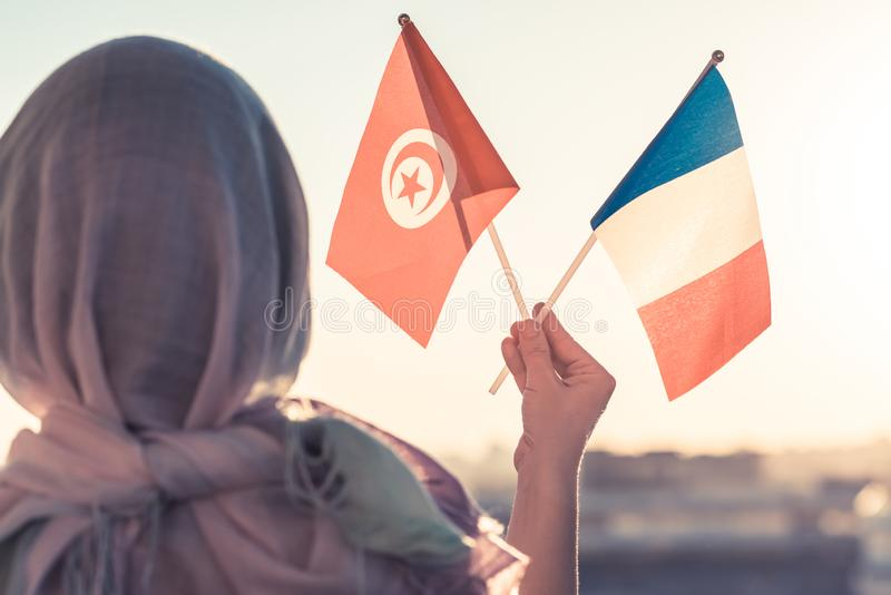 Muslim woman in scarf with Tunisia and French flags of at sunset.Concept. Muslim woman in scarf with Tunisia and French flags of at sunset.Concept stock photos