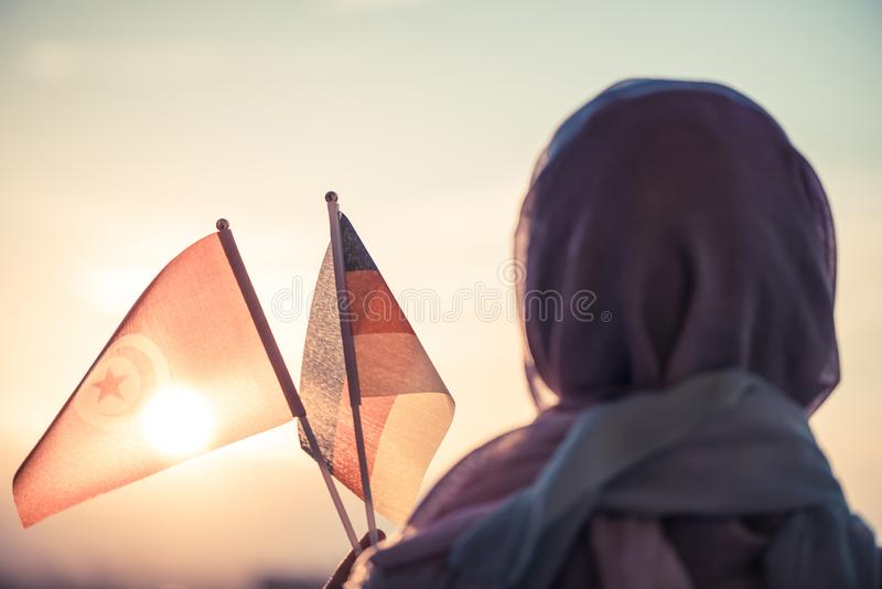 Muslim woman in scarf with Tunisia and Germany flags of at sunset.Concept.  stock image