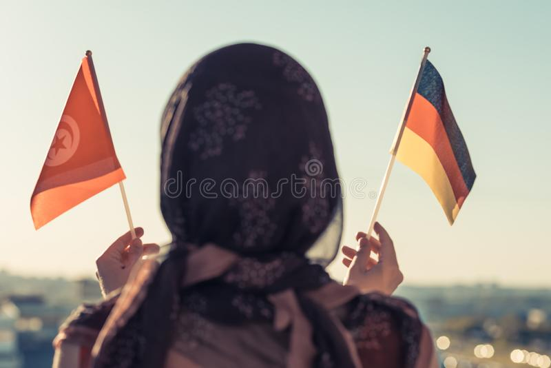 Muslim woman in scarf with Tunisia and Germany flags of at sunset.Concept. Muslim woman in scarf with Tunisia and Germany flags of at sunset.Concept royalty free stock photography