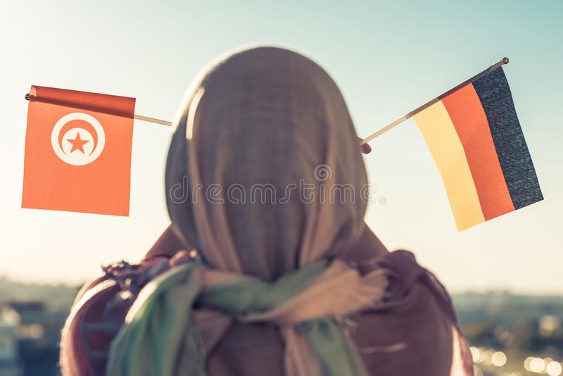 Muslim woman in scarf with Tunisia and Germany flags of at sunset.Concept. Muslim woman in scarf with Tunisia and Germany flags of at sunset.Concept stock photography