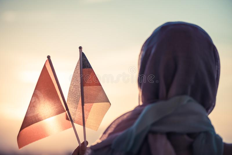 Muslim woman in scarf with Tunisia and Germany flags of at sunset.Concept. Muslim woman in scarf with Tunisia and Germany flags of at sunset.Concept royalty free stock images
