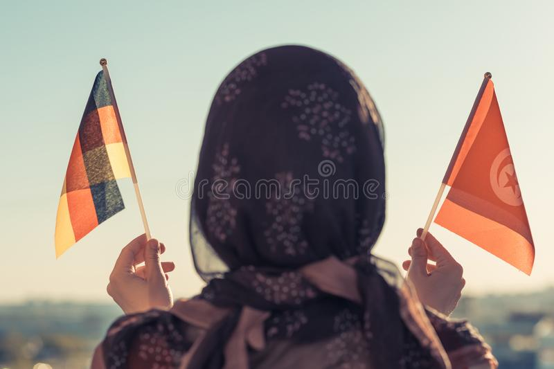 Muslim woman in scarf with Tunisia and Germany flags of at sunset.Concept. Muslim woman in scarf with Tunisia and Germany flags of at sunset.Concept royalty free stock photo