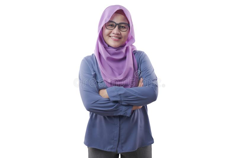 Muslim woman Smiling Friendly With Crossed Arms. Asian muslim woman wearing blue shirt and purple hijab smiling friendly with arms crossed, confident successful royalty free stock image