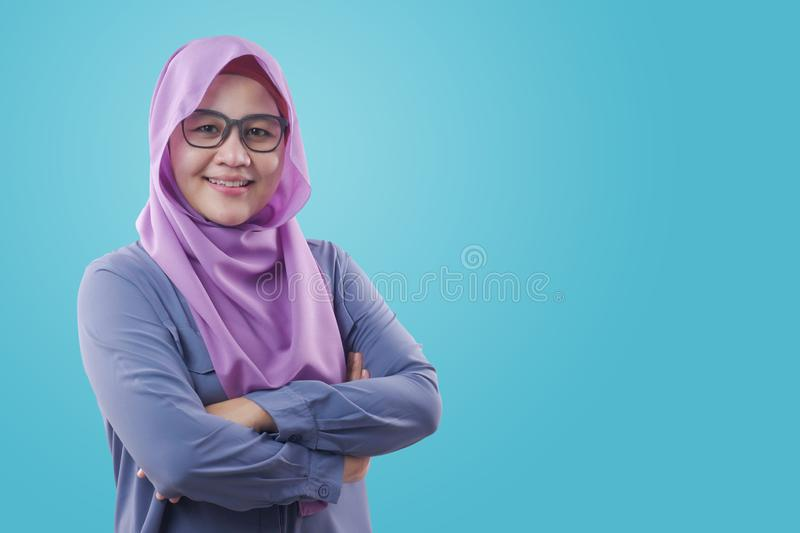 Muslim woman Smiling Friendly With Crossed Arms. Asian muslim woman wearing blue shirt and purple hijab smiling friendly with arms crossed, confident successful royalty free stock photo