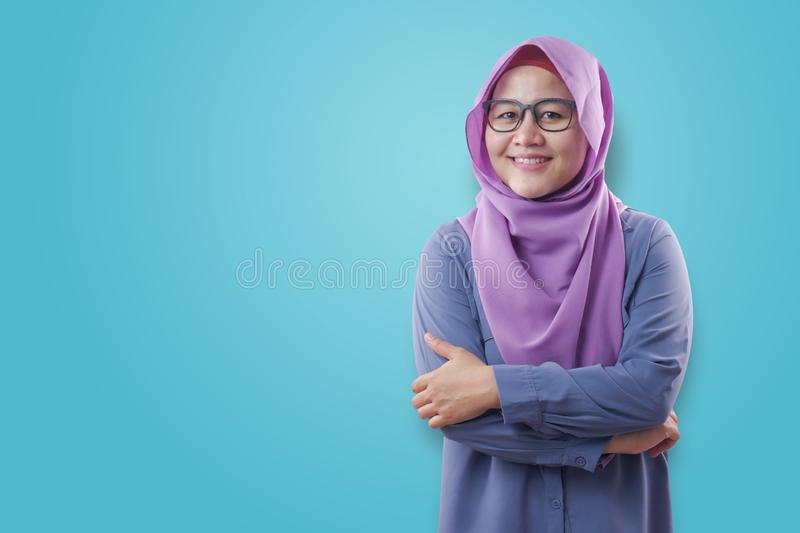 Muslim woman Smiling Friendly With Crossed Arms. Asian muslim woman wearing blue shirt and purple hijab smiling friendly with arms crossed, confident successful stock photos