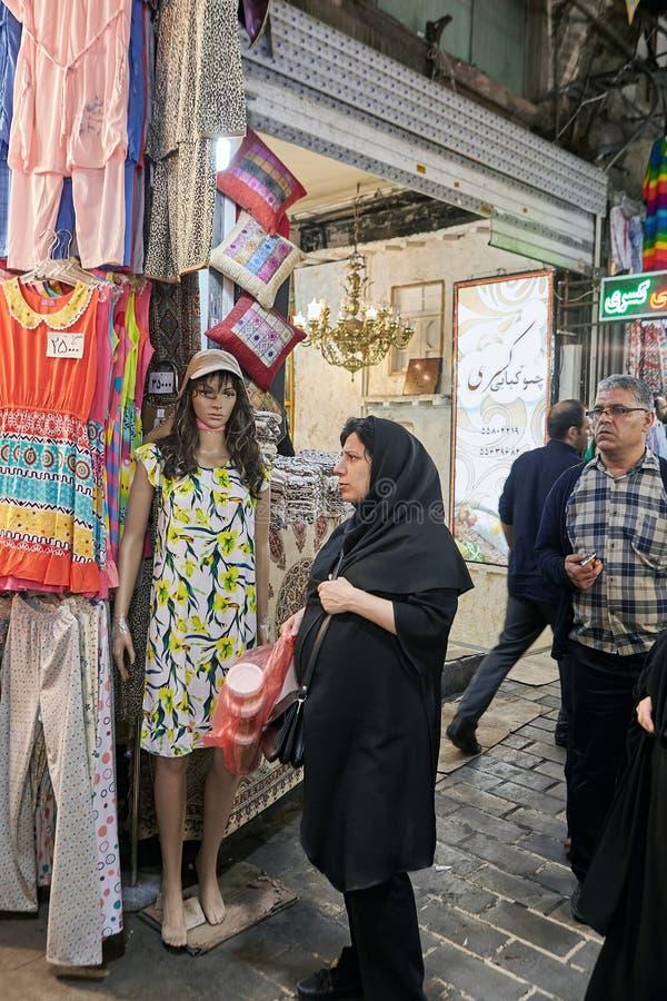 Muslim woman stands near mannequin wearing summer dress, Tehran, Iran. royalty free stock photography