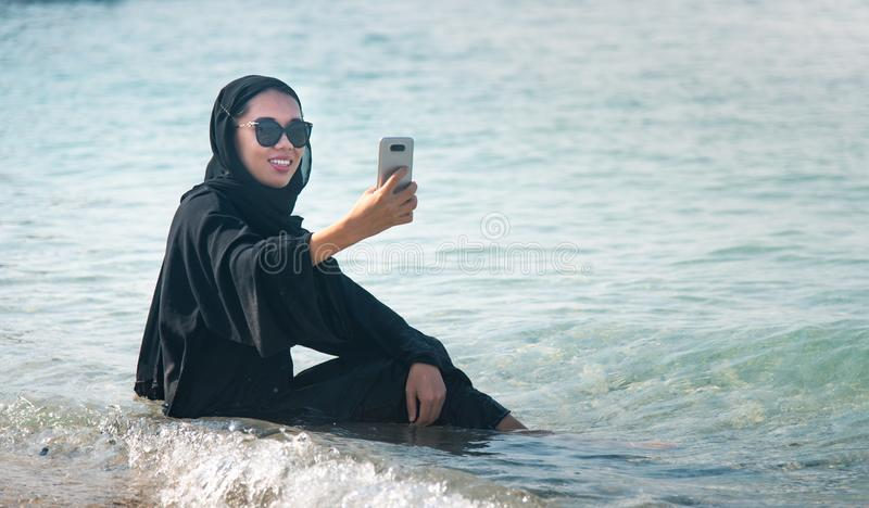 Muslim woman taking selfie on the beach. In hijab, abaya, water, sea, seaside, phone, malaysian, asian, beautiful, happy, holiday, girl, female, summer, people stock photos