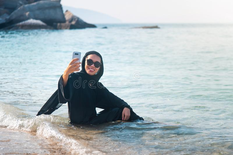 Muslim woman taking selfie on the beach. In hijab, abaya, water, sea, seaside, phone, malaysian, asian, beautiful, happy, holiday, girl, female, summer, people royalty free stock photography
