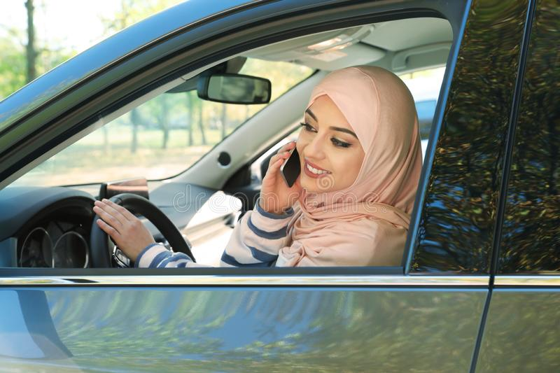 Muslim woman talking on phone in driver`s seat. Of car royalty free stock photography