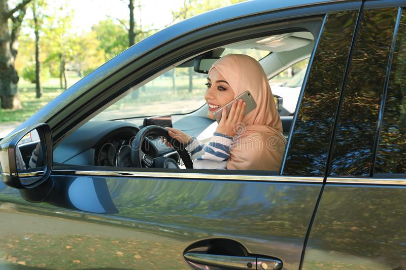 Muslim woman talking on phone in driver`s seat. Of car stock photo
