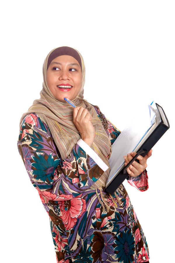 Muslim woman in thinking pose. Beautiful mature Muslim woman in thinking pose with files and books in hand royalty free stock photos