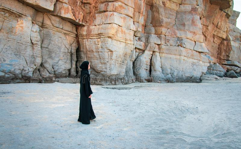 Muslim woman walking on the beach. With rocky background, sand, asian, abaya, hijab, malaysian, indonesian, person, female, copy, dress, rocks, shade, lifestyle stock photography