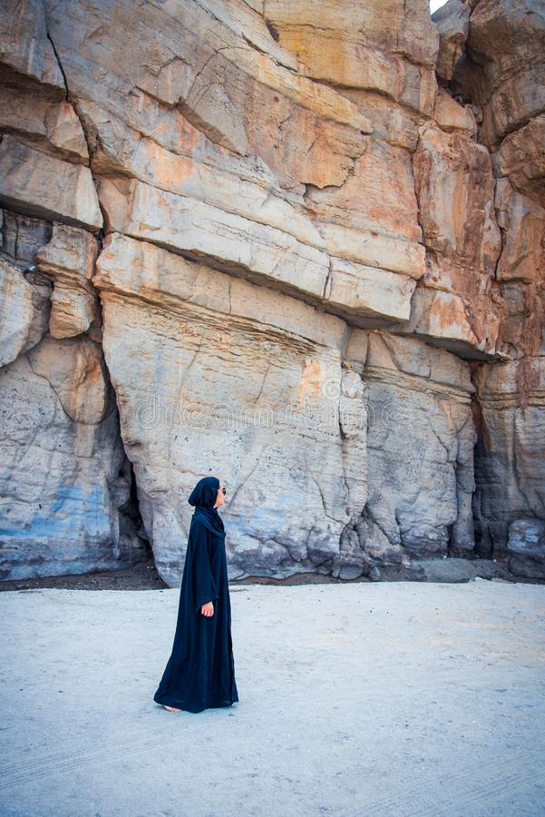 Muslim woman walking on the beach. With rocky background, sand, asian, abaya, hijab, malaysian, indonesian, person, female, copy, dress, rocks, shade, lifestyle stock images
