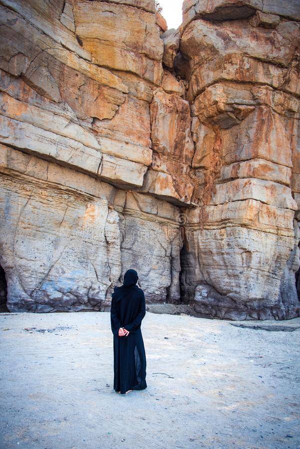 Muslim woman walking on the beach. With rocky background, sand, abaya, hijab, person, female, copy, dress, rocks, shade, lifestyle, space, uae, religion, gulf royalty free stock photo