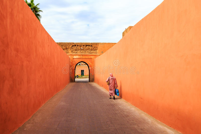 Muslim woman walking through a narrow street with gate in Marrakech royalty free stock photography