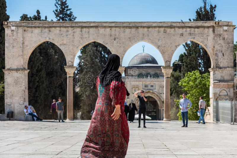 Muslim woman walking out of  the square of the Golden Dome of the Rock royalty free stock photos