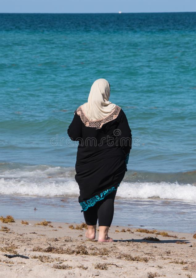 Muslim woman in black robe and white head scarf looking out at b stock photography