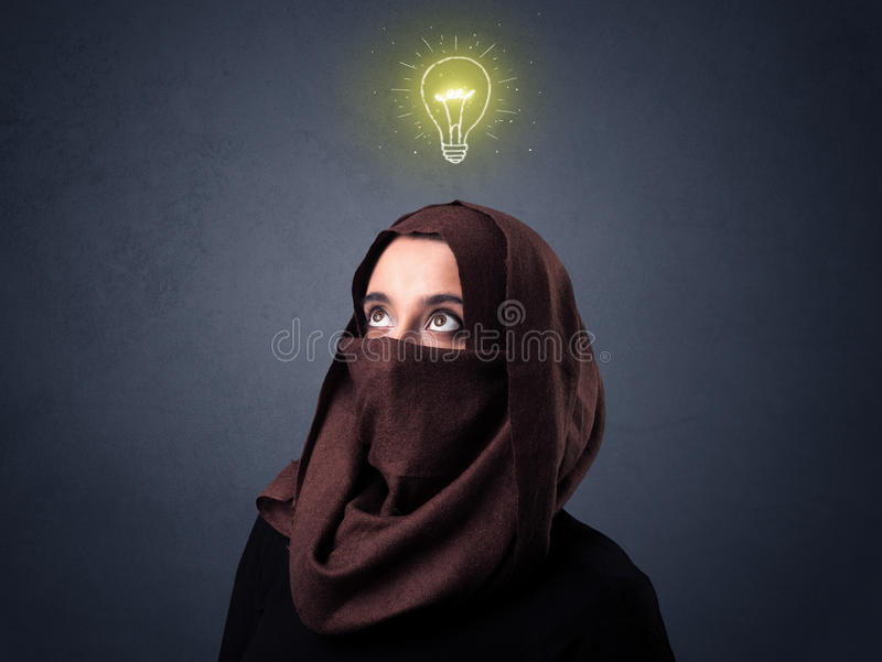 Muslim woman wearing niqab. Young muslim woman wearing niqab with lit lightbulb above her head stock image