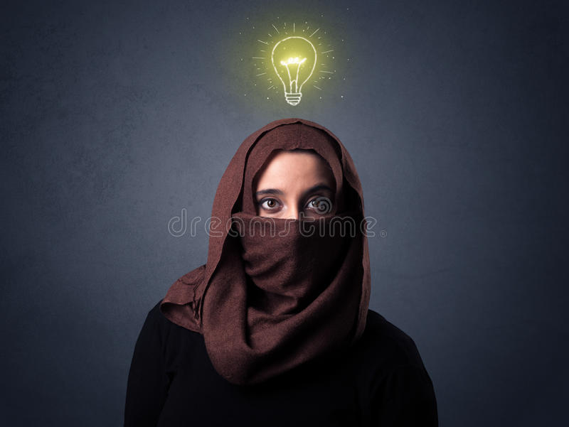 Muslim woman wearing niqab. Young muslim woman wearing niqab with lit lightbulb above her head royalty free stock photo