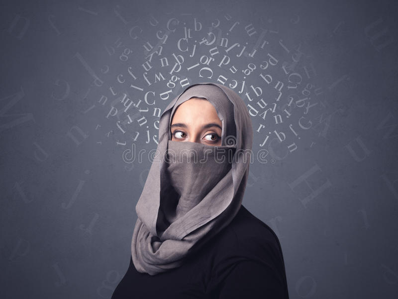 Muslim woman wearing niqab. Young muslim woman wearing niqab with white alphabet letters above her head stock photo