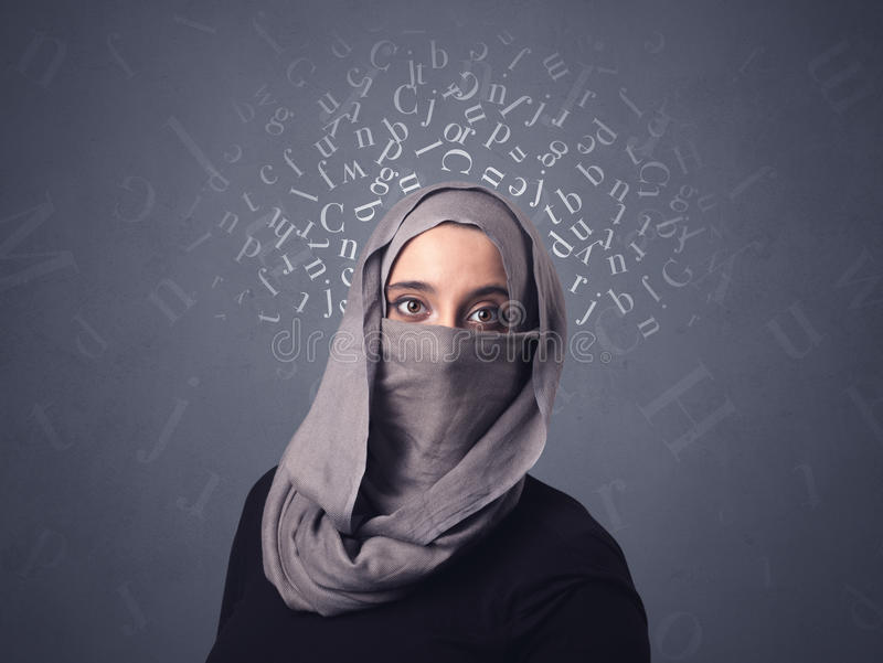 Muslim woman wearing niqab. Young muslim woman wearing niqab with white alphabet letters above her head royalty free stock photography
