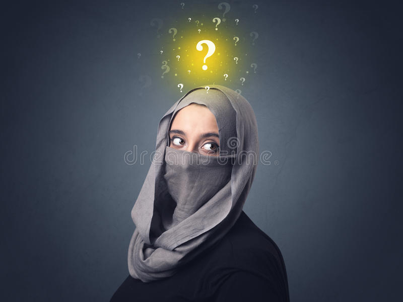 Muslim woman wearing niqab. Young muslim woman wearing niqab with yellow question marks above her head stock photos