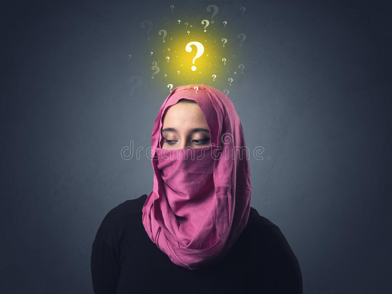Muslim woman wearing niqab. Young muslim woman wearing niqab with yellow question marks above her head stock image