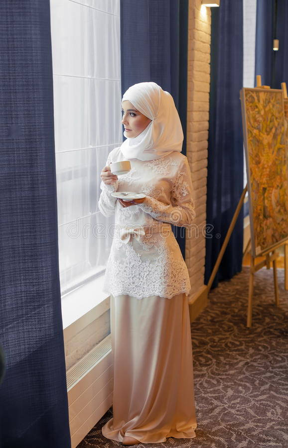 Muslim woman in a white wedding dress with a cup of tea in his hands. In a hotel stock photography
