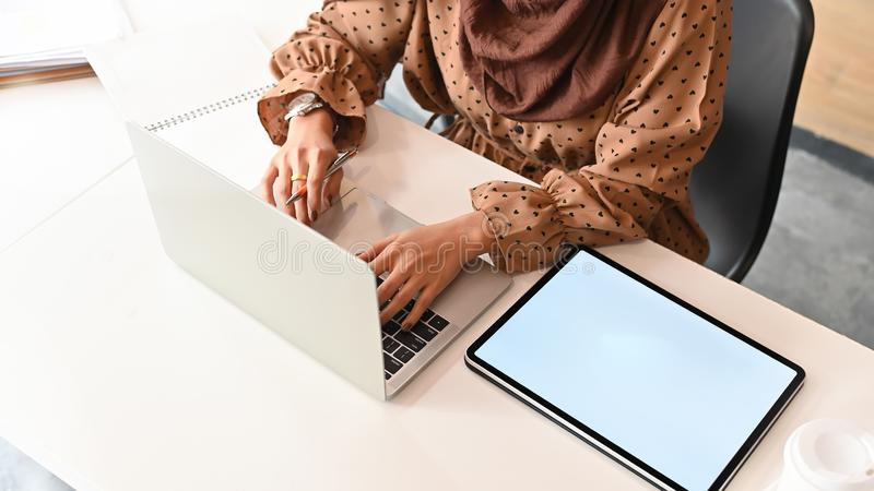 Muslim woman working with laptop computer on work table and Close up top view shot.  stock images