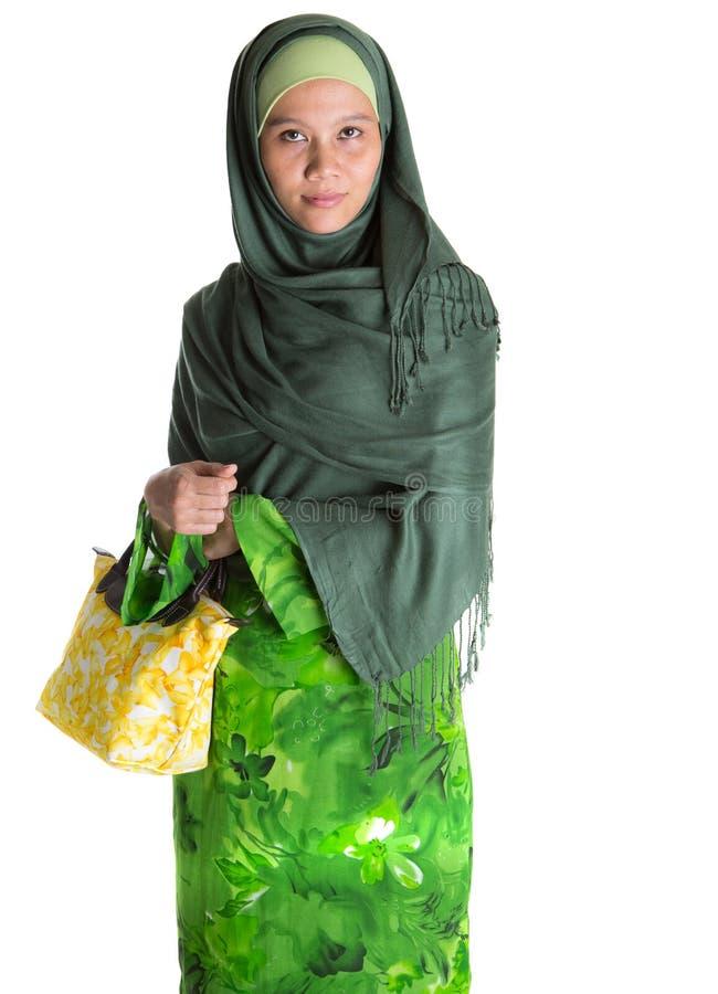 Muslim Woman With Yellow Handbag III. Muslim woman in green dress, hijab with yellow handbag over white background stock images