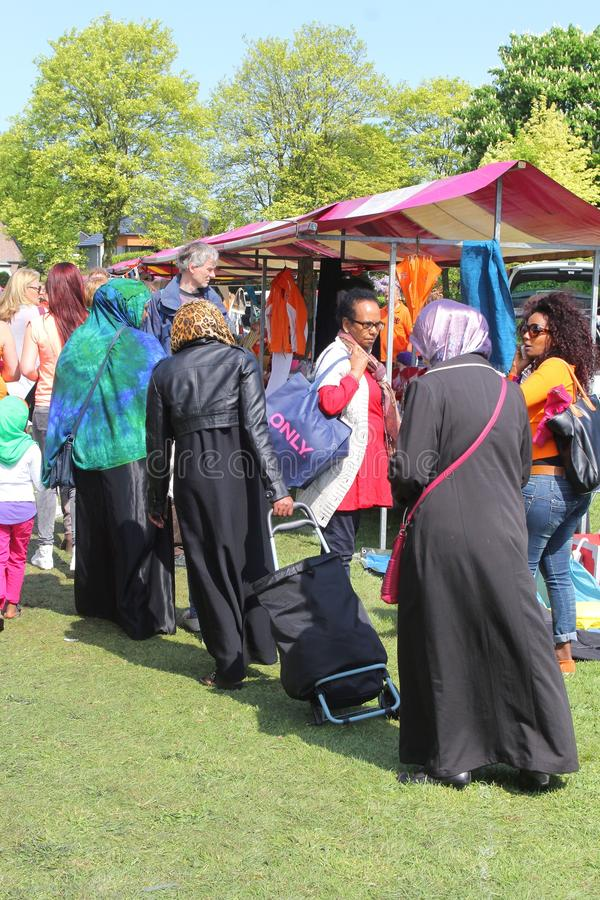 Multicultural society, women and diversity at the market in the Netherlands. Muslim women and Antillian women are shopping at the market in the Netherlands stock photography