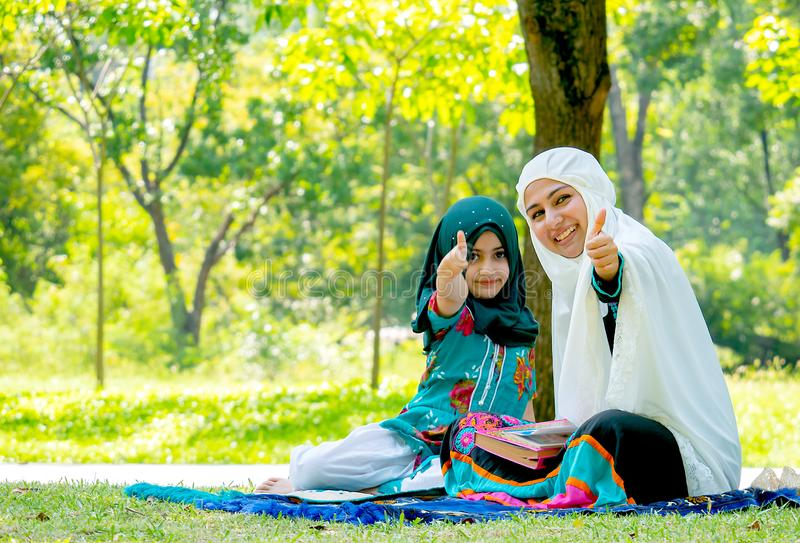Muslim woman and girl show thumps up to the camera during reading some books in the garden stock photography
