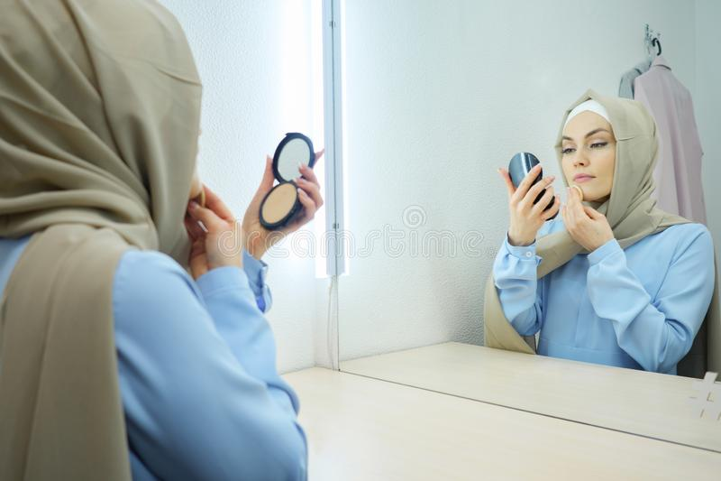 Muslim young attractive woman in beige hijab and traditional blue dress making make-up stock photo