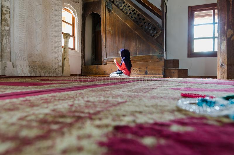 Muslim young girl is praying in mosque royalty free stock images