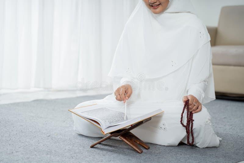 Muslim young woman praying in white traditional clothes. Muslim young woman praying while sitting in white traditional clothes royalty free stock image