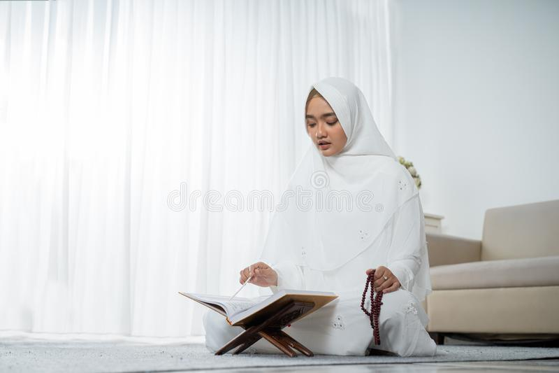 Muslim young woman praying in white traditional clothes. Muslim young woman praying while sitting in white traditional clothes royalty free stock images