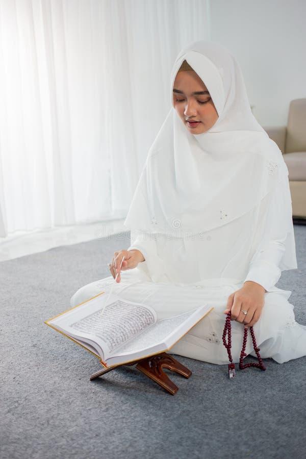 Muslim young woman praying in white traditional clothes. Muslim young woman praying while sitting in white traditional clothes royalty free stock photos