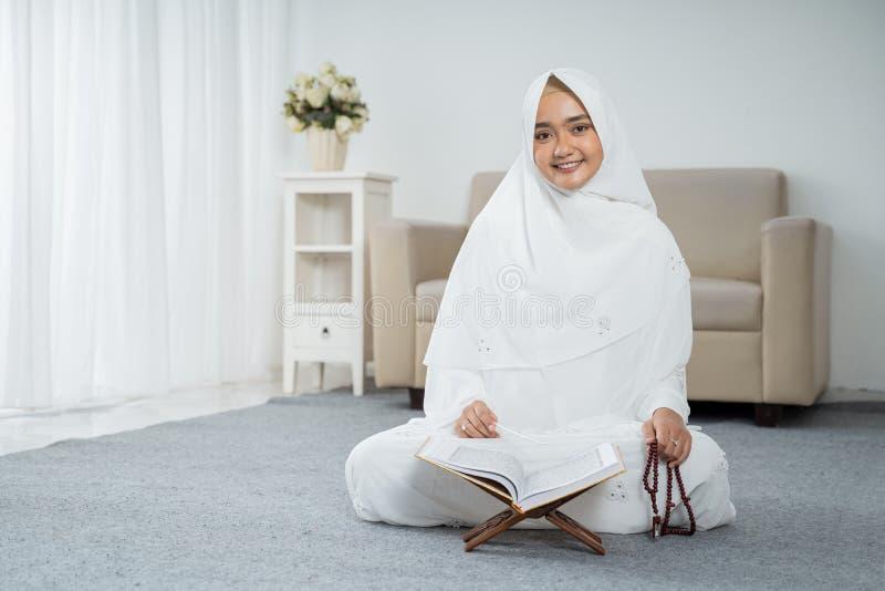 Muslim young woman praying in white traditional clothes. Muslim young woman praying while sitting in white traditional clothes stock photography