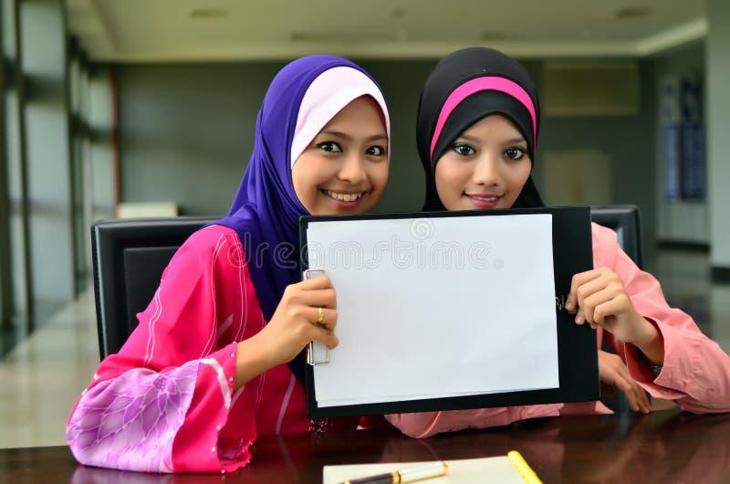 Muslimah拿着白色卡片的女商人微笑 免版税库存照片