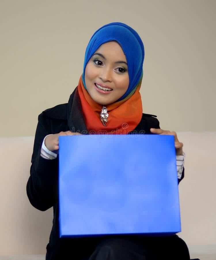Muslimah顶头围巾的女商人有蓝色委员会的 库存照片