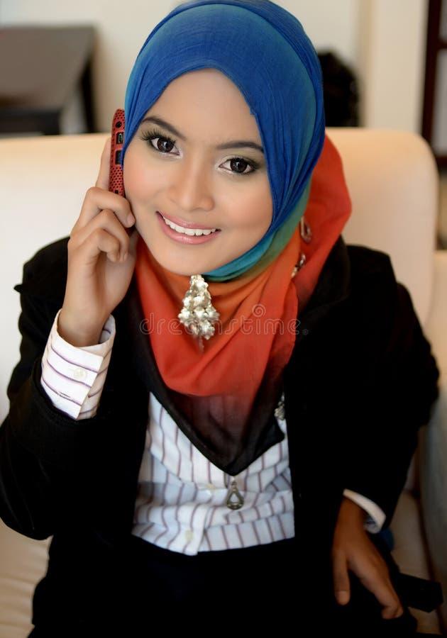 Muslimah affärskvinna i den head halsduken med mobiltelefonen arkivbild