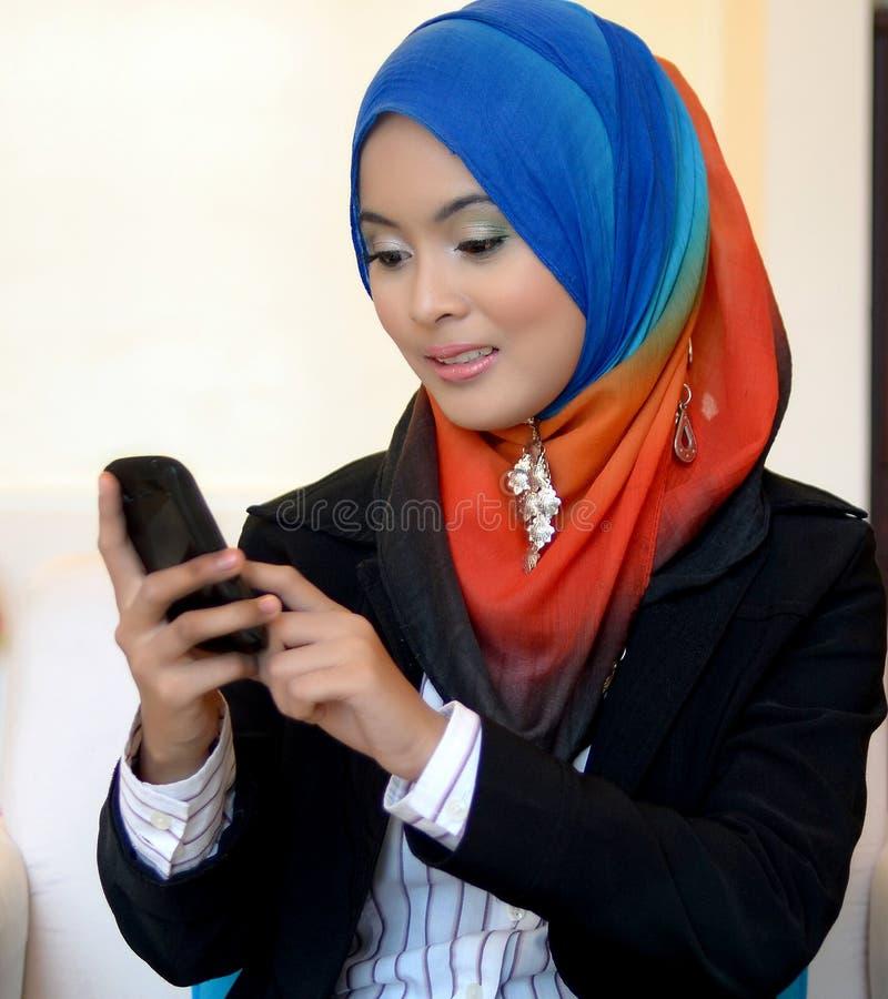 Muslimah affärskvinna i den head halsduken med mobiltelefonen arkivbilder